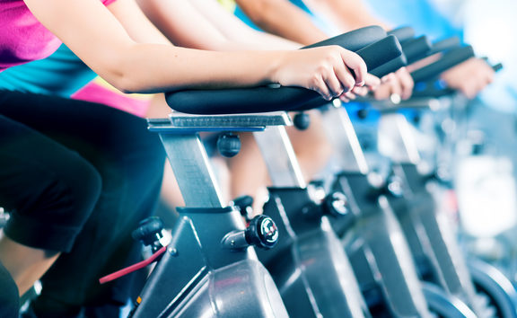 Group of four people spinning in the gym, as they take part in a HIIT class.