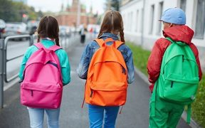 A photo taken from behind of three girls with brightly coloured clothes and backpacks walking down a street.