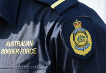 An Australian Border Force (ABF) badge can be seen on an officer's shirt.