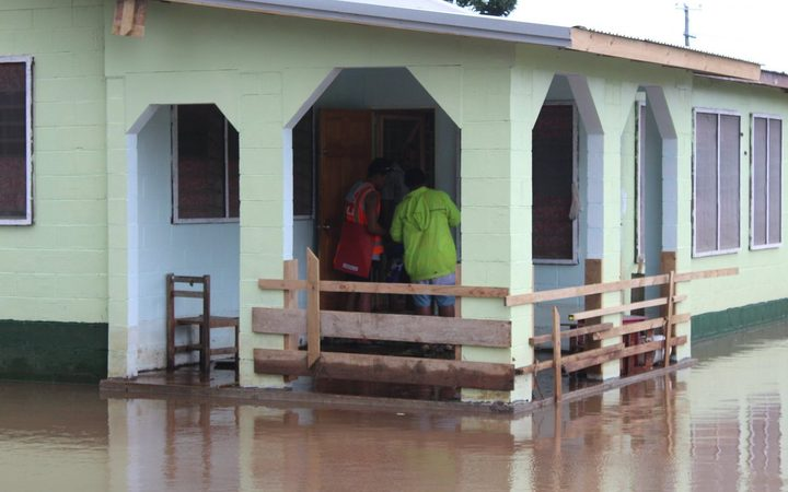 Red Cross workers go door to door in Samoa to check on residents in the wake of Cyclone Gita