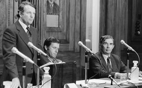Prime Minister Bill Rowling delivers an outline of the Labour government's economic policy in 1975 with ministers Colin Moyle (centre) and Michael Connelly (right) seated beside him. Rowling rejected retrenchment and defended heavy overseas borrowing as necessary to protect New Zealanders' jobs.