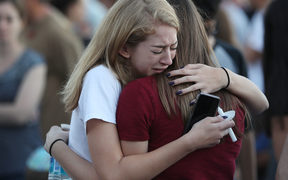 People hug as they attend a candlelight memorial service for the victims of the shooting at Marjory Stoneman Douglas High School that killed 17 people on February 15, 2018 in Parkland, Florida.