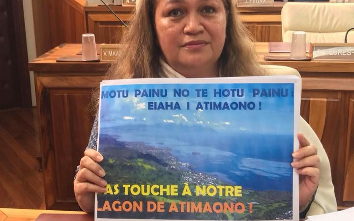 French Polynesian opposition politician Valentina Cross holds a poster expressing her opposition to a proposed floating island project.