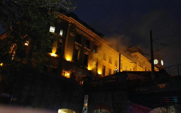 Smoke billows out of Sydney's Central Railway Station, lit by yellow lights.