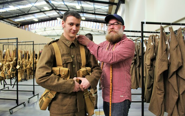 Private (PTE) Simon Adams is fitted into his replica First World War uniform, supplied by WingNut Films, by costume assistant Paul Booth.