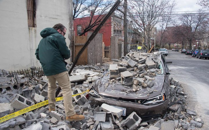 An insurance company employee checks the damage to a car after a partially burnt building collapsed due to strong winds in Northeast Washington, DC, on March 2, 2018.