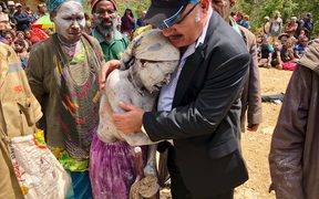 Peter O'Neill comforts a woman in an area affected by the 7.5 quake.