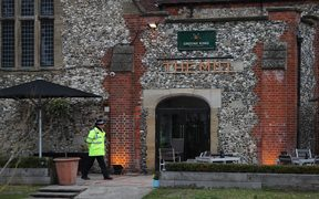 A police officer stands in front of The Mill pub in Salisbury, southern England. Diners are being told to wash their possessions.