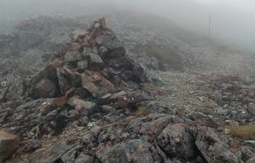 An image of a rock cairn, high on a ridge line, very useful for identifying the trail.