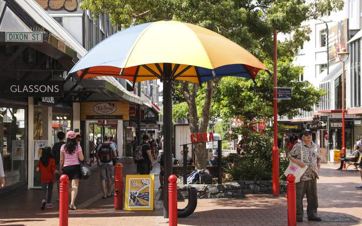 Summer in Wellington, Cuba Street. A man seeks shelter from the sun.