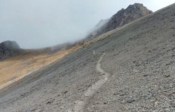 An image of a sheer scree slope with a barely-there trail on the side.
