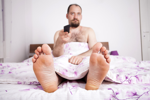 A man watches television in bed - remote in hand.