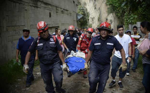 Rescuers carry a victim after a landslide at Cambray village
