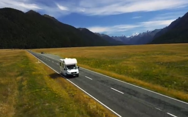 A camper van is seen driving on the wrong side of the road in a Tourism New Zealand video.