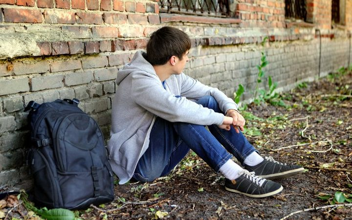 45247047 - sad teenager near the brick wall of the old house