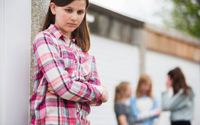 A photo of a sad looking teenage girl in the foreground. Behind her is a group of other girls talking
