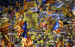 People wave Catalan pro-independence 'estelada' flags during a demonstration to support Catalan pro-independence jailed leaders and politicians and called by 'Espai Democracia i Convivencia' platform that groups separatist collectives and unions in Barcelona on April 15, 2018.