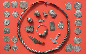 Some of the silver treasures from Schaprode, including a coiled ring, silver beads, cut-up silver jewellery, Thor's hammer amulet, and Danish and Ottonian coins.