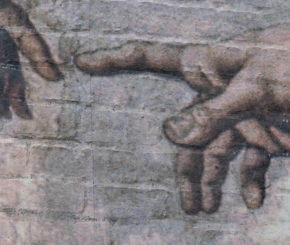 Finger of god painted on a wall in Auckland, a replica of Adam's Creation Sistine Chapel ceiling' by Michelangelo.