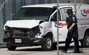 Police inspect a van which mounted the pavement and hit a crowd of pedestrians in Toronto.