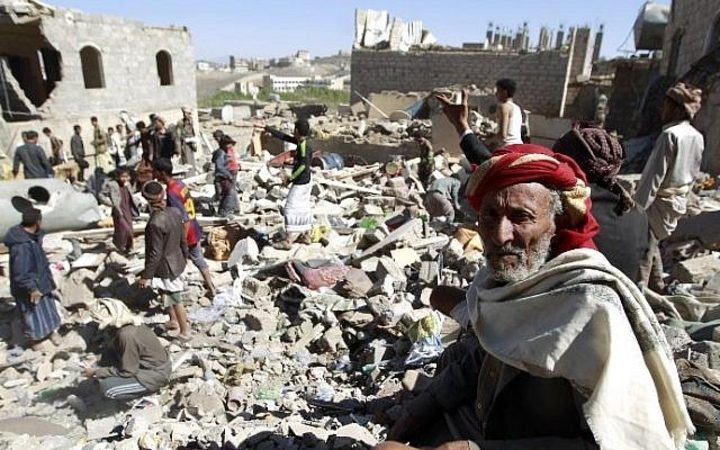 A Yemeni man sits on the rubble as people search for survivors in houses destroyed by a Saudi-led air strike on a residential area in Yemen's capital,