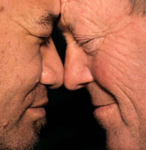 Two older men, one Māori and one Pākehā, hongi.