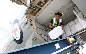 LAC Zinzan Currey unloads water containers from a RNZAF Boeing 757 at Bauerfield Airport, Port Vila, Vanuatu, part of an 11 tonne delivery of relief supplies for Ambae Island.