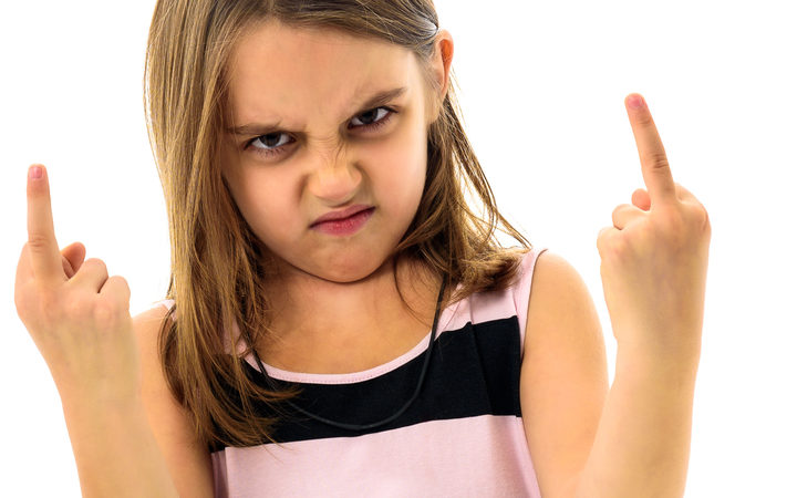 Little young girl is angry, mad, disobedient with bad behaviour. Children making the act of insubordination and disobedience, yelling, flipping off, showing the middle finger. Act of giving the finger.