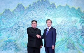 South Korea's President Moon Jae-in (R) shakes hands with North Korea's leader Kim Jong Un (L) during the Inter-Korean summit in the Peace House building on the southern side of the truce village of Panmunjom on April 27, 2018.