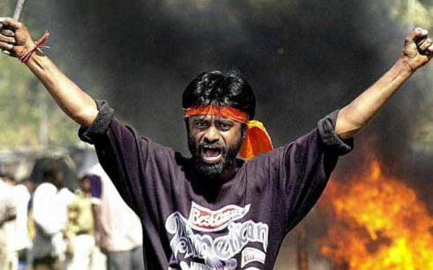 This picture taken 28 February 2002 shows an IndianBajranj Dal activist armed with a iron stick shouting slogans against muslims as they went burning muslim shops and attacked residences at Sahapur in Ahmedabad.