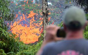 A man watches as lava is seen spewing from a fissure in the Leilani Estates subdivision near the town of Pahoa on Hawaii's Big Island on May 4, 2018. / AFP PHOTO / Frederic J. BROWN