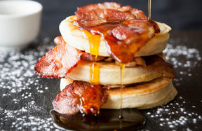 Female hand pouring maple syrup over breakfast bacon crumpet on slate