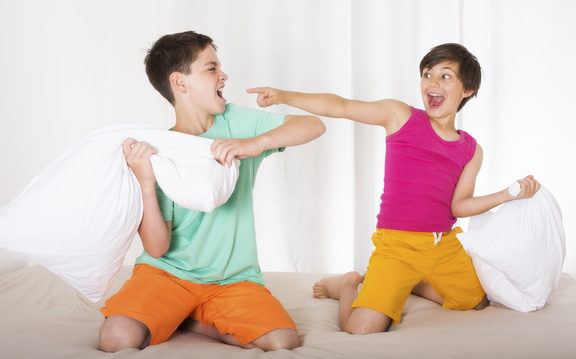 A photo of two brothers having a pillow fight and laughing