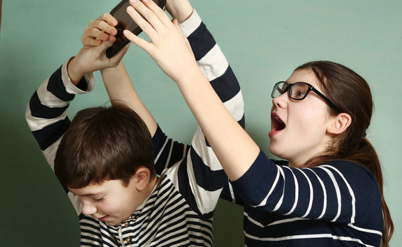65478991 - teen siblings couple brother and sister in glasses fighting because of tablet try to take it for gaming