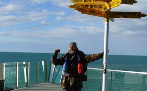 Bruce Hopkins poses underneath the Bluff signpost, the official end of Te Araroa.