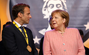 France's President Emmanuel Macron stands next to German Chancellor Angela Merkel at the end of the Charlemagne prize award ceremony on May 10, 2018 in Aachen, western Germany.