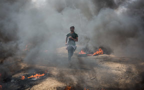 A young protester runs away from tear gas thrown by Israeli soldiers in Gaza.