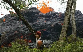 A lava fissure erupts as a resident stands nearby