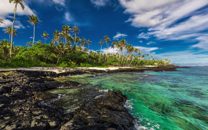 Beach with coral reef and black volcanic rocks on south side of Upolu, Samoa Islands