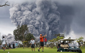People play golf as an ash plume rises in the distance from the Kilauea volcano on Hawaii's Big Island.