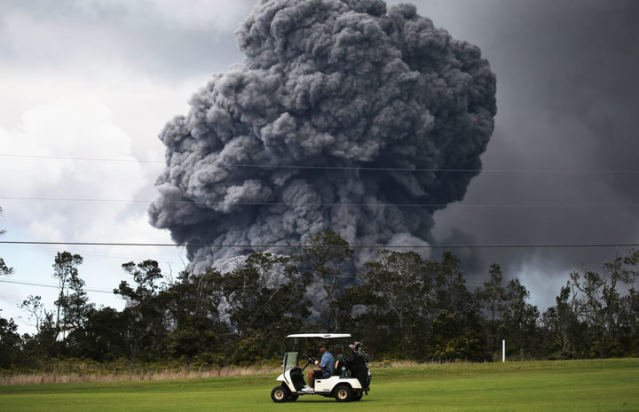 A man drives a golf cart at a golf course as an ash plume rises in the distance from the Kilauea volcano on Hawaii's Big Island on May 15, 2018