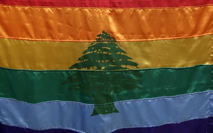 A gay pride flag bearing the cedar tree of the Lebanese flag carried by a human rights activists during an anti-homophobia rally in Beirut in 2013.