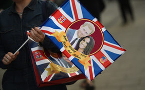 A visitor carries a bag featuring Britain's Prince Harry and US actress Meghan Markle as the country prepares for the Royal Wedding.