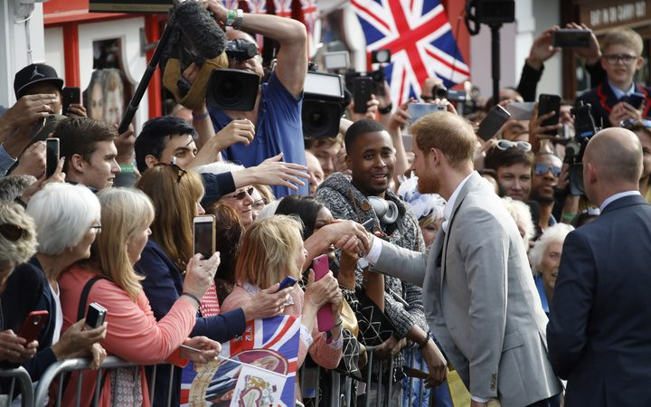 Prince Harry greets well-wishers on the street outside Windsor Castle ahead of marrying Meghan Markle.