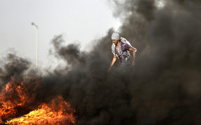 A Palestinian demonstrator walks in the billowing smoke during clashes with Israeli forces along the border of the Gaza strip.