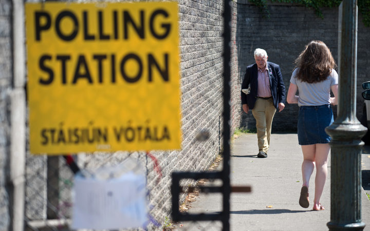Voters arrive and leave St. Patrick's Boys National School polling station in Drumcondra, Dublin, to vote in the Irish referendum on liberalising abortion law on 25 May.