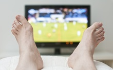 A person with their feet up watching sports on television.