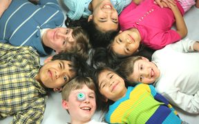 A photo of seven mixed race children all lying with their heads in a circle