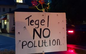 A sign reading 'no pollution' held by a protester at outside a hui held by Tegel in Auckland on Wednesday 6 June 2018.