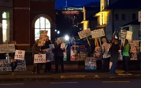 Protesters opposing a proposed chicken farm near Dargaville hold placards and chant outside a hui held by Tegel in Auckland on Wednesday 6 June 2018.
